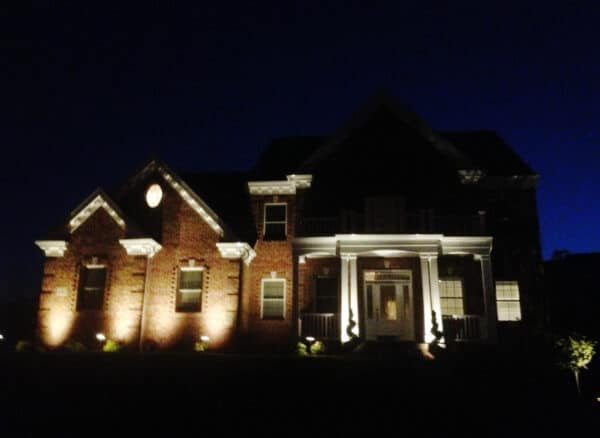 home with white pillars and low voltage lighting at night